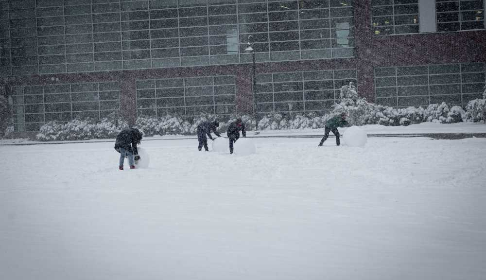 Students start building a snowman on the Quad.