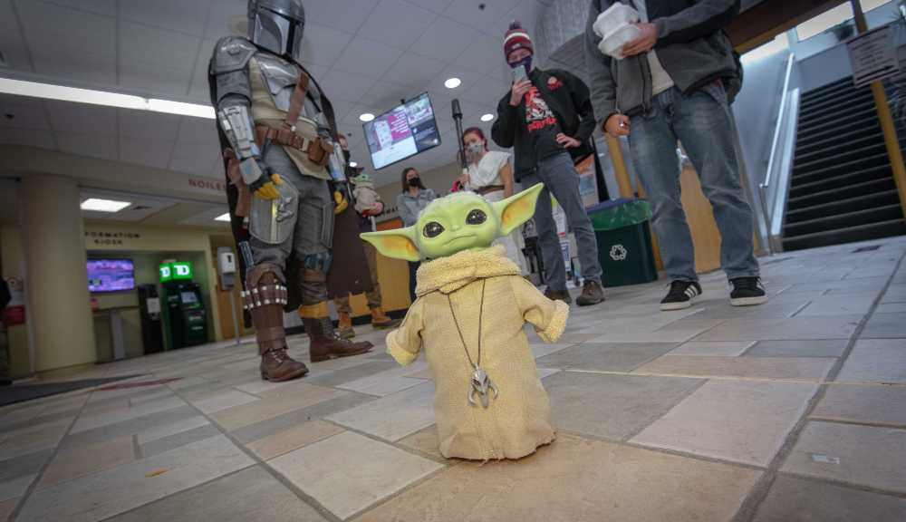Students and staff dressed as Star Wars characters gather behind a Baby Yoda figure in the campus center.