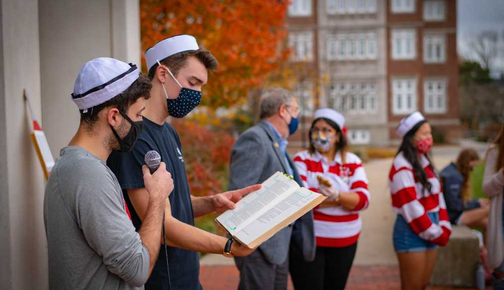 Two students wearing face coverings read from WPI's Two Towers book during Founders Day.