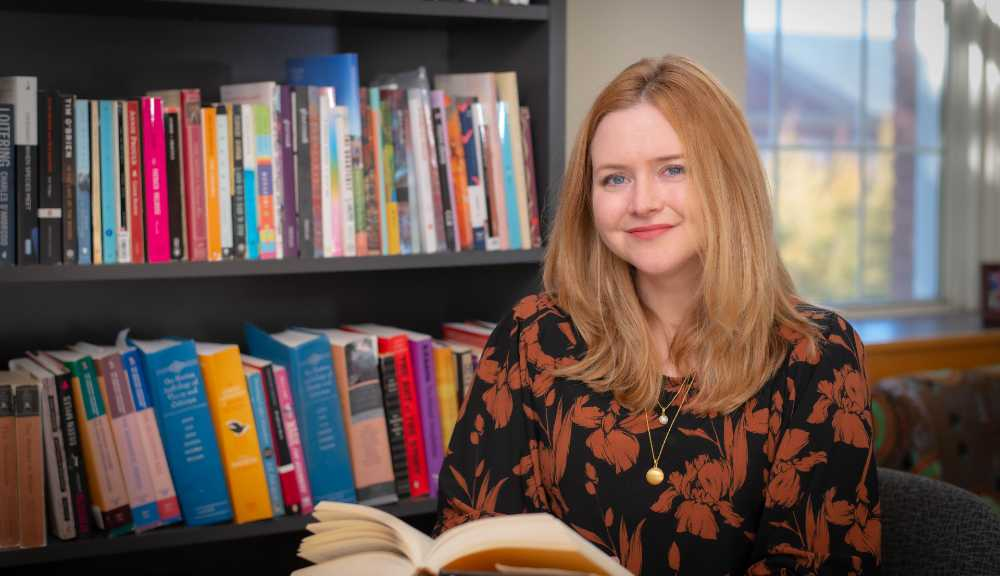 Kate McIntyre poses with an open book in her hands and a full bookshelf behind her.