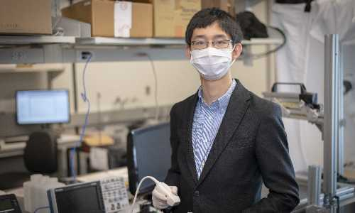 Haichong Zhang poses in the lab while wearing a face covering.