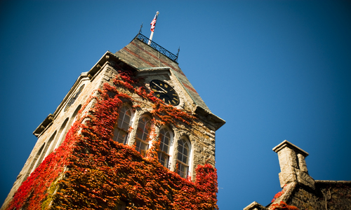 Boynton Hall Tower covered in red ivy with a blue sky background