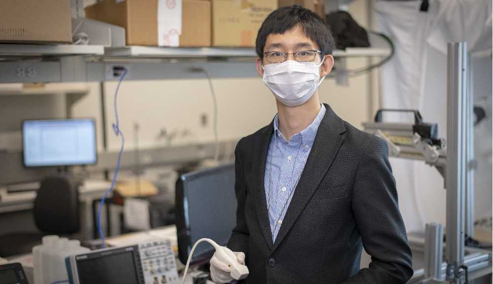 Haichong Zhang wears a face covering while holding part of the robotic ultrasound machine he and his team are working on.
