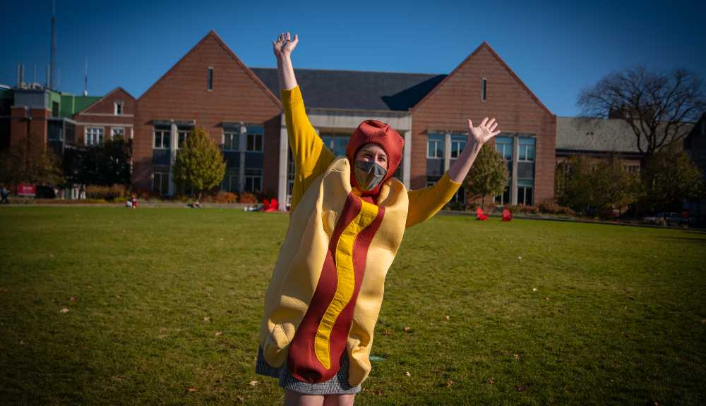 Emily Perlow poses on the Quad with her hands in the air while wearing a face covering and a hot dog costume.
