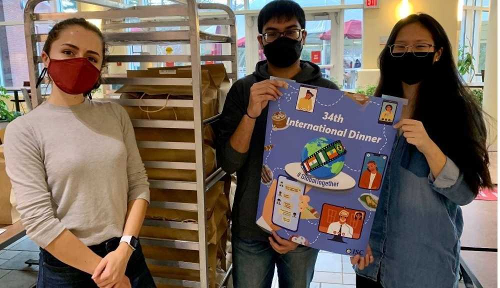 Students wearing face coverings pose with an international dinner sign in front of trays of food.