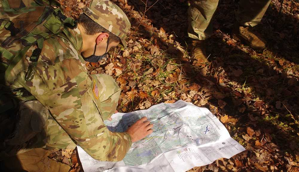 An ROTC cadet studies a map on the ground at Fort Devens.