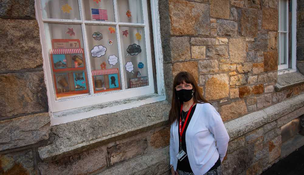 A staff member wearing a face covering poses in front of some Founders Day window art at Boynton Hall.