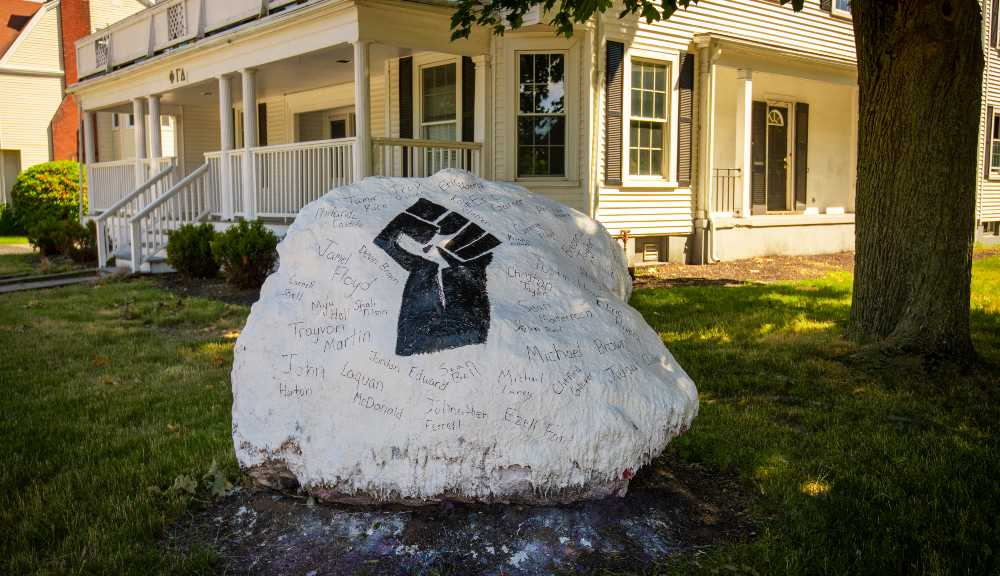 A large rock is painted white with the Black power fist painted in black in the middle.