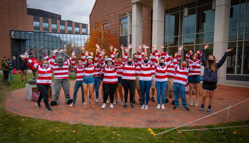 Students from SAS don their face coverings and red-and-white striped shirts and pose together with Gompei.