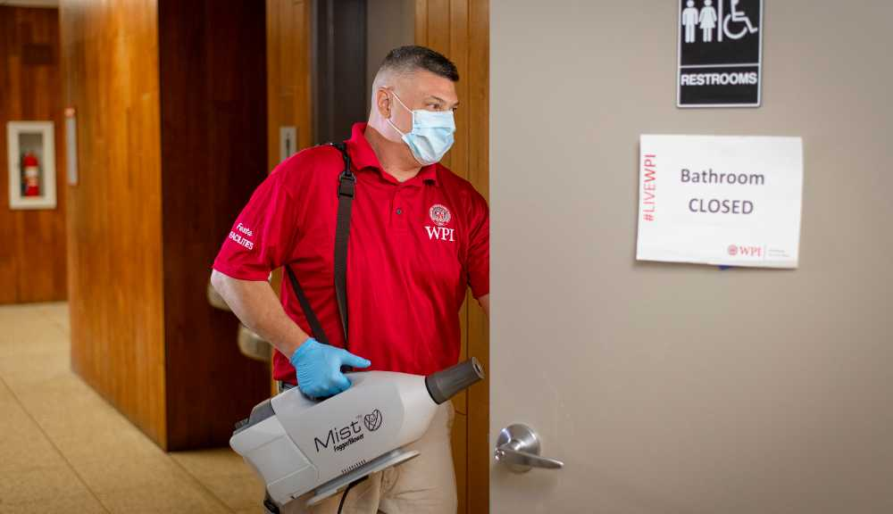 A member of the facilities team enters a restroom to sanitize it.