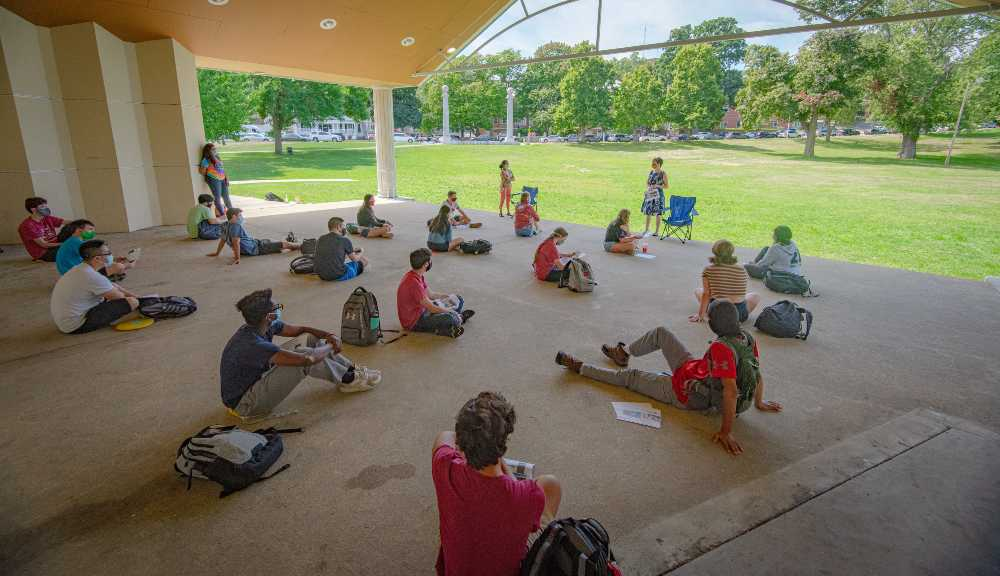 Students gather for an outdoor class while keeping social distance.