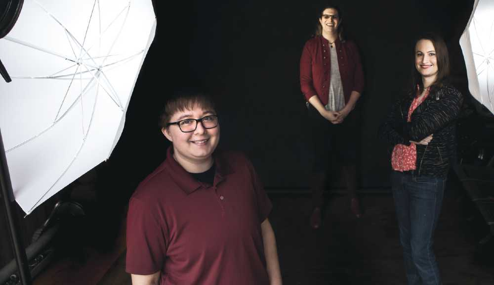 Three WPI alumni smile up at the camera against a black background as part of a photoshoot for the WPI Journal.