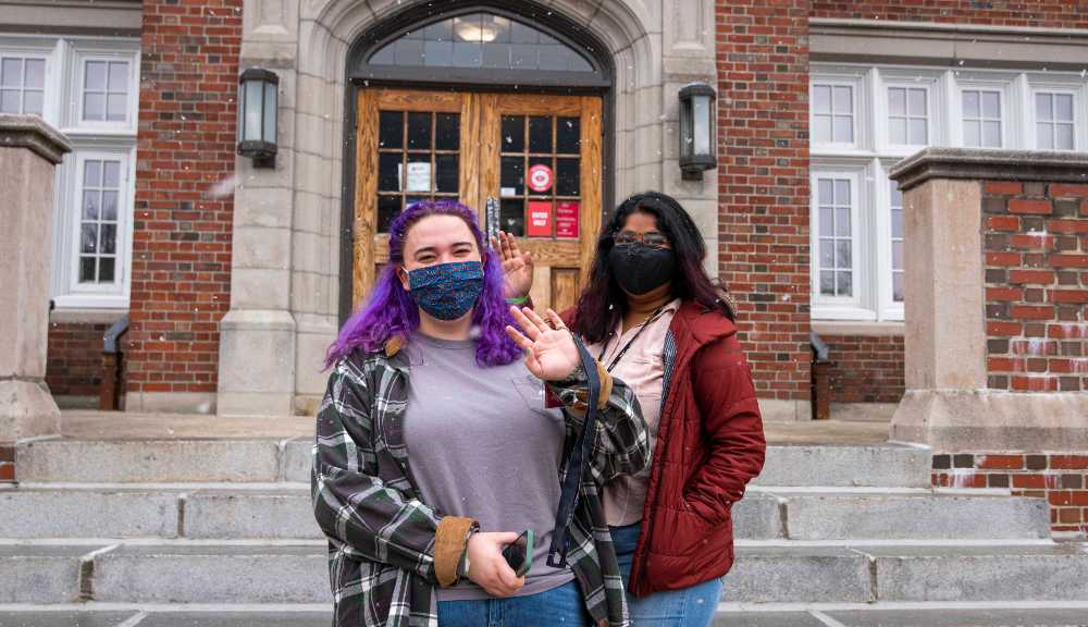 Two WPI students wearing masks wave at the camera during move-in.