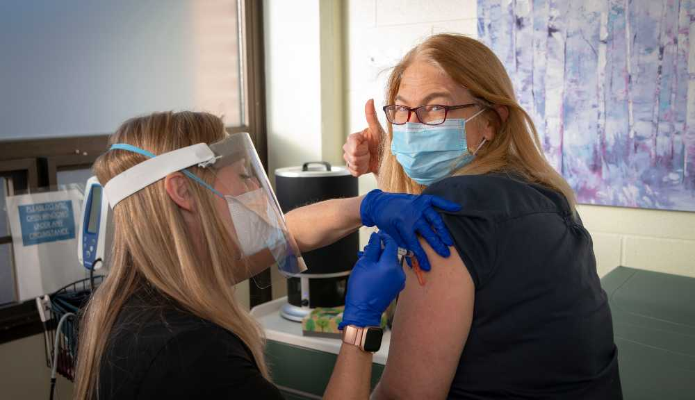 A woman receives a COVID-19 vaccine at WPI while wearing a mask.