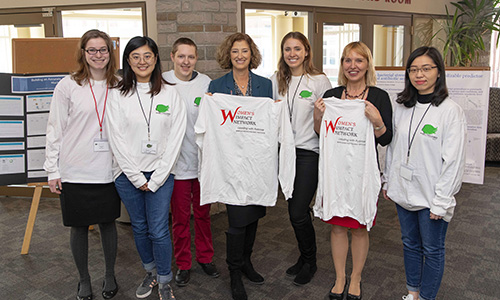 Students presenting faculty with Women in Data Science t-shirts