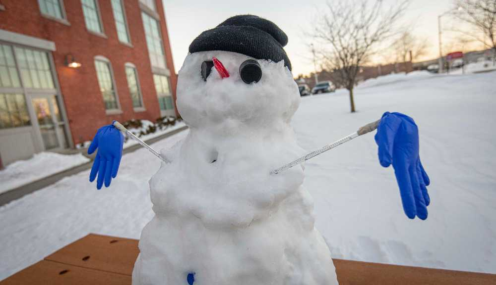 A small snowman sits outside of Gateway Park.