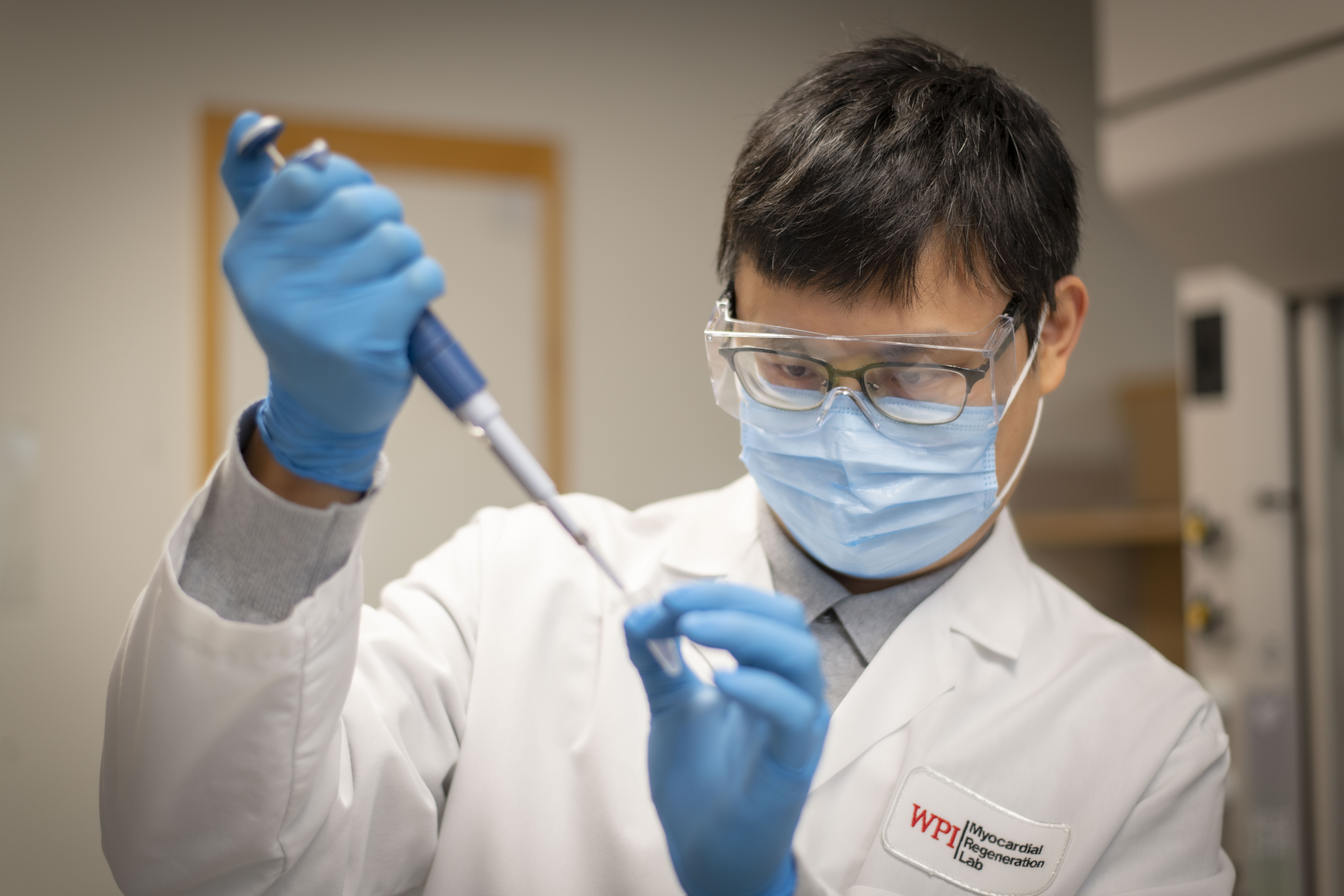 Kun-Ta Wu works in the lab while wearing PPE.