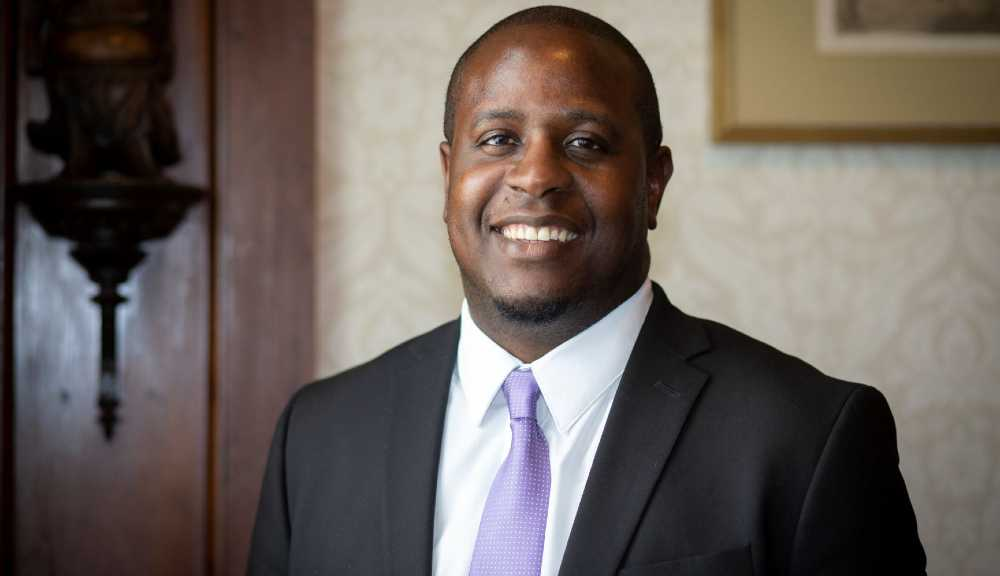 A photo of Kola Akindele smiling in a suit and tie.