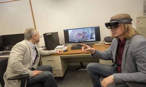 TWO MEN LOOKING AT A COMPUTER, ONE WEARING VIRTUAL REALITY HEADGEAR