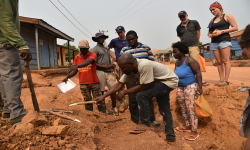 Students and community members digging a trench