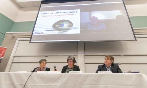THREE FACULTY MEMBERS AT A PANEL WITH A SCREEN BEHIND THEM