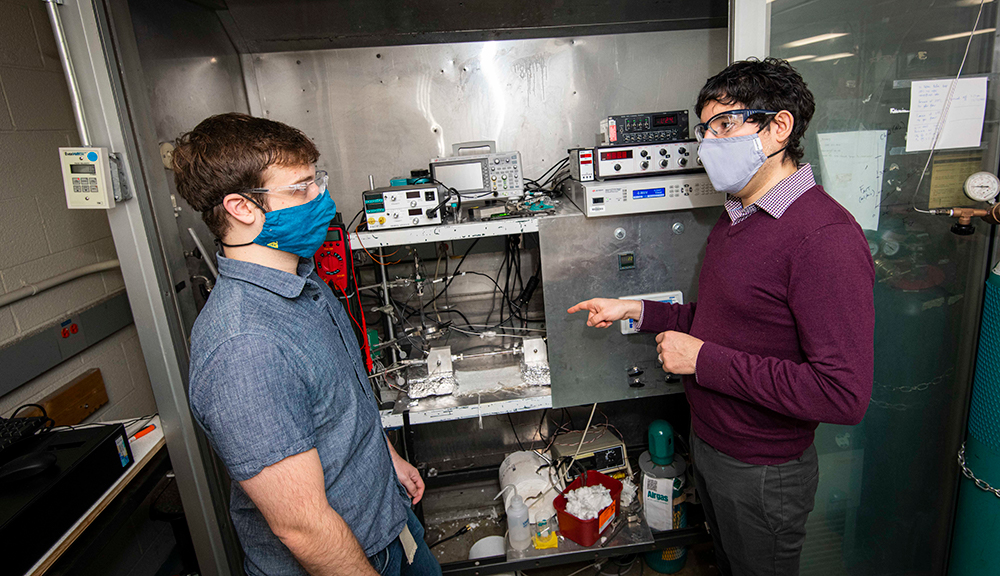 WPI professor Andrew Teixeira (right) confers with PhD student Cameron Armstrong, who custom built an ultrafast micro catalytic reactor to produce ammonia.