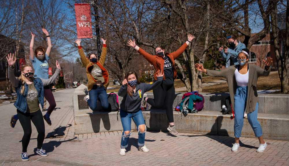 Several students jump up in the air together near the fountain on campus.