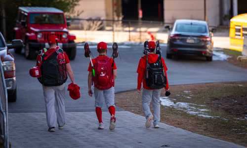 A shot of three baseball players carrying their equipment.