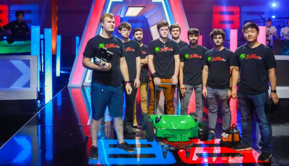 Team Ribbot gathers on the BattleBots stage with their robot in front of them.