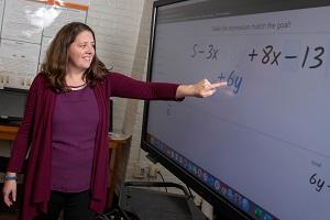 Erin Ottmar points to a digital screen. alt