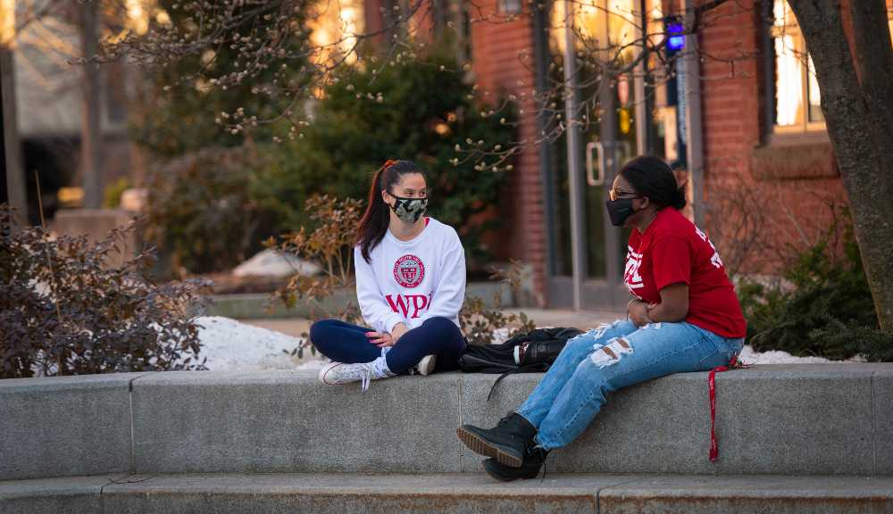 Two WPI students converse near the fountain on campus.