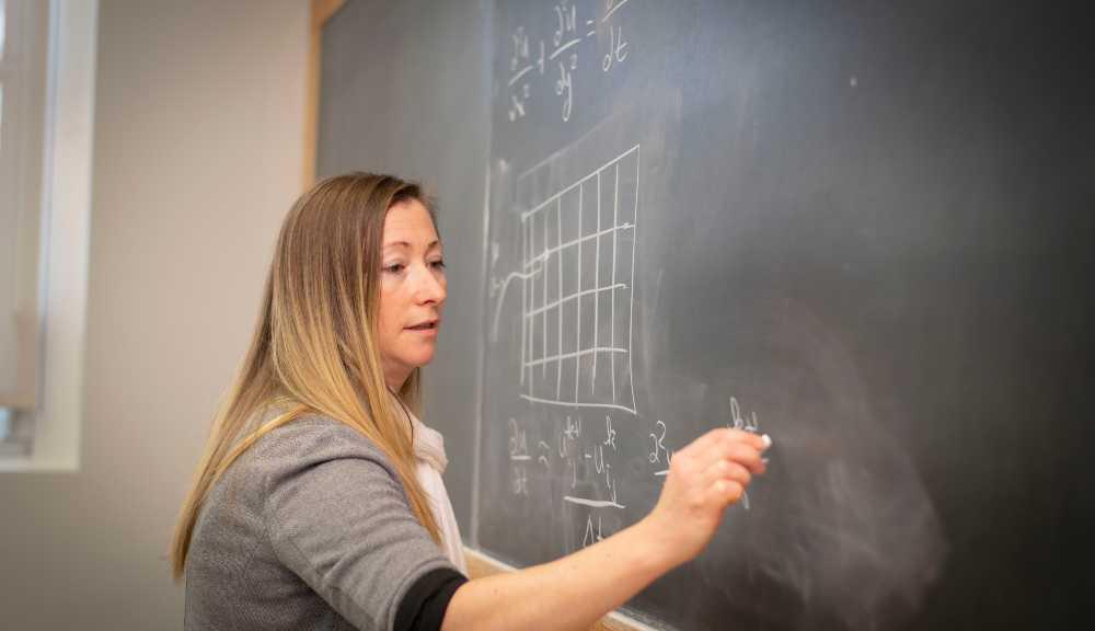 Sarah Olson writes out an equation on a blackboard.