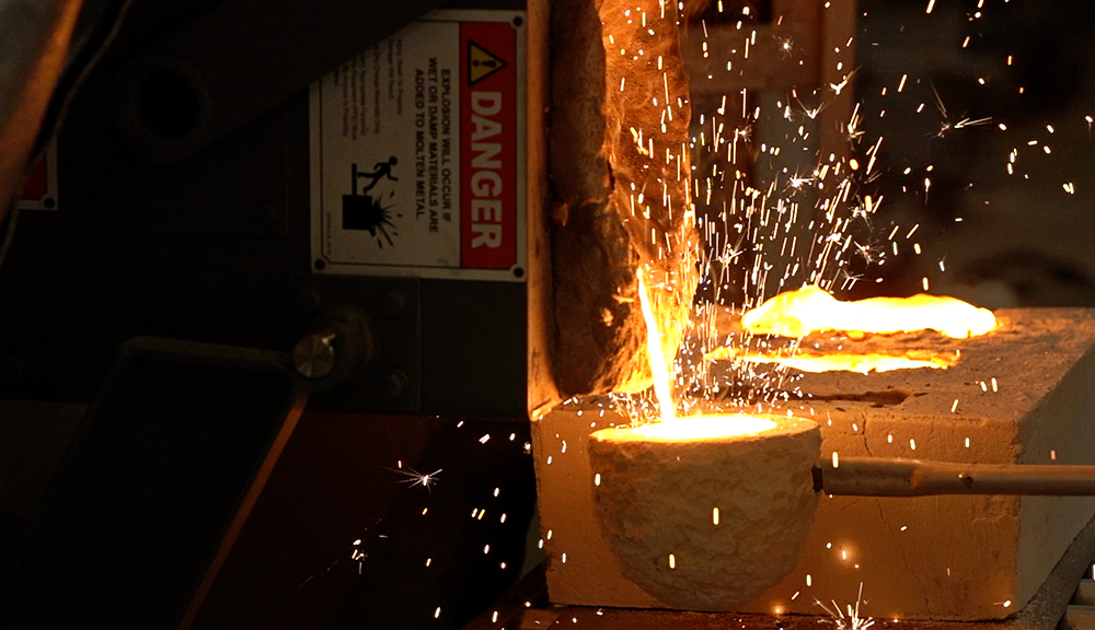 Pouring the extra molten metal into a ceramic spoon for future casting. alt