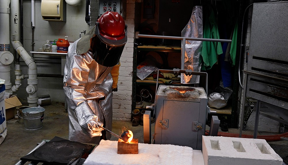 Pouring molten steel into a copper sample maker for chemical composition testing. alt