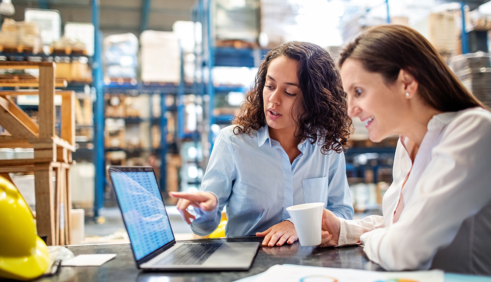 Two women working on a laptop in a warehouse