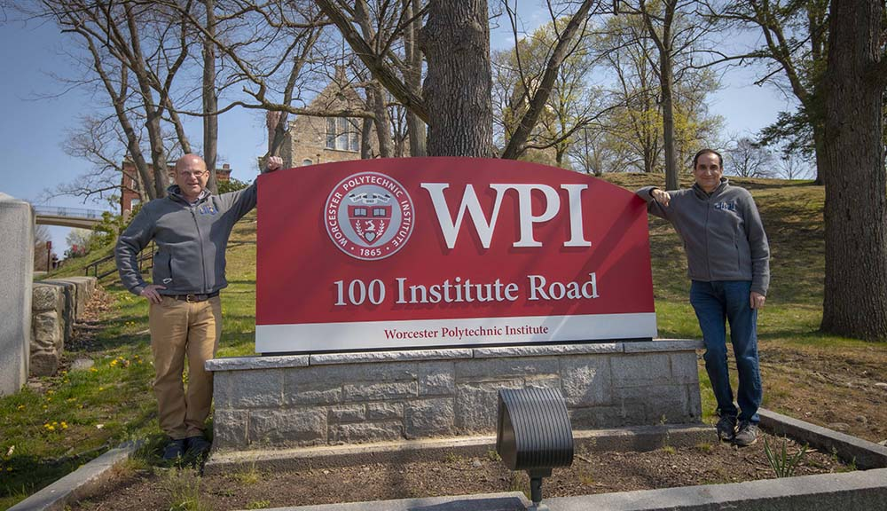 Tim Loew and Monty Sharma stand six feet apart in front of the WPI sign on Institute Road. alt