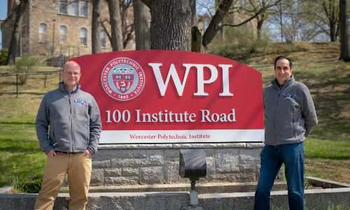 Tim Loew and Monty Sharma stand in front of the WPI sign on Institute Road.