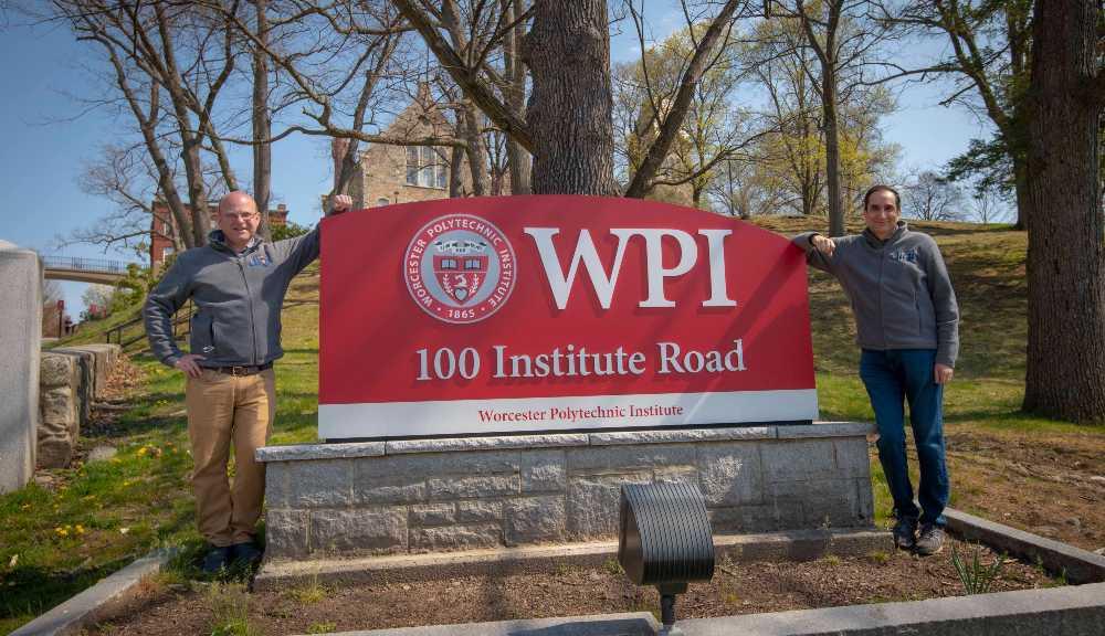 Tim Loew and Monty Sharma of MassDigi pose outside the WPI sign on Institute Road.