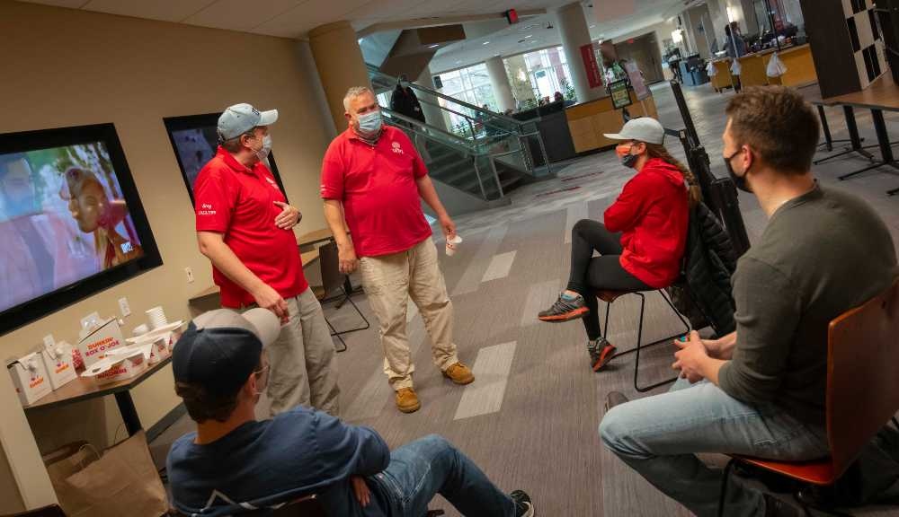 Students chat with members of the Facilities team during their morning break.