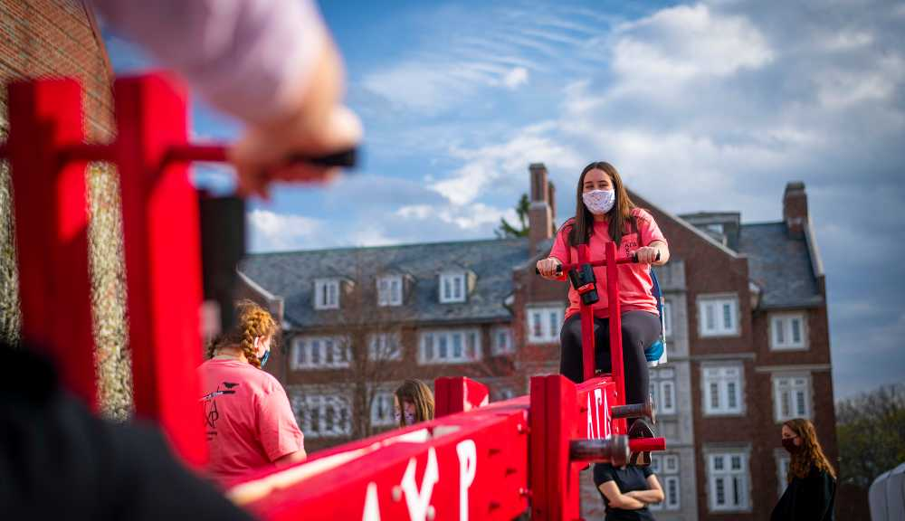 A photo of a student on a giant seesaw as part of a week-long teeter-tottering event for charity.