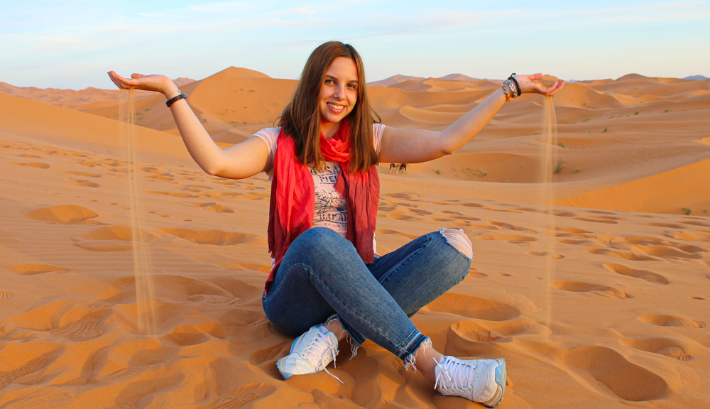 Marina Como sits in the desert smiling, holding her hands up with sand running through her fingers.