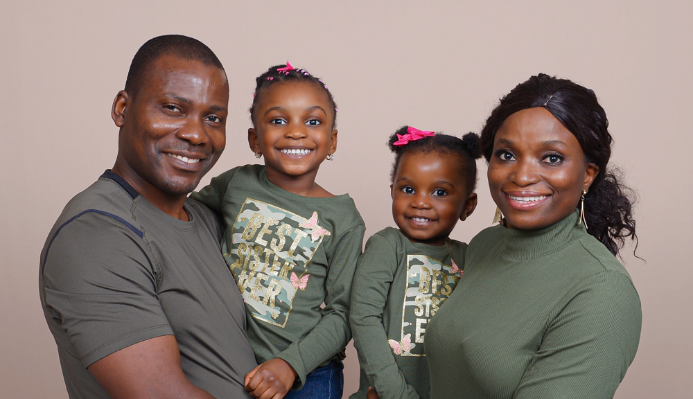 Deborah Oyewole smiles with her husband and two daughters.