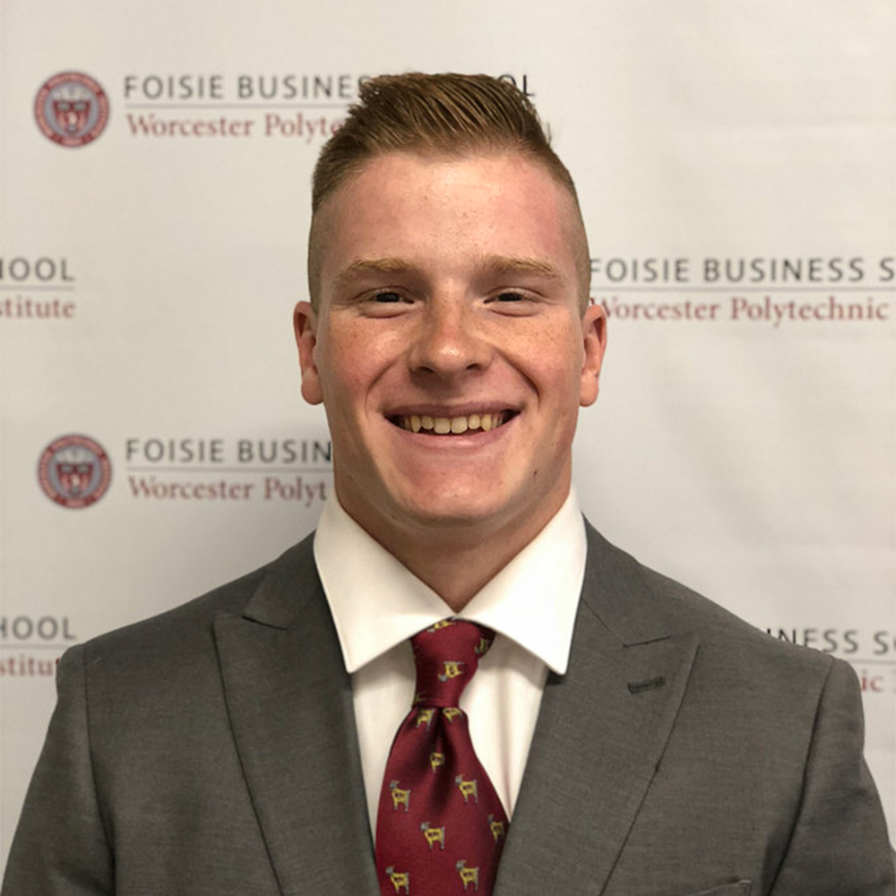 Johann Bradley smiles in a suit and tie in front of a Foisie Business School banner background.