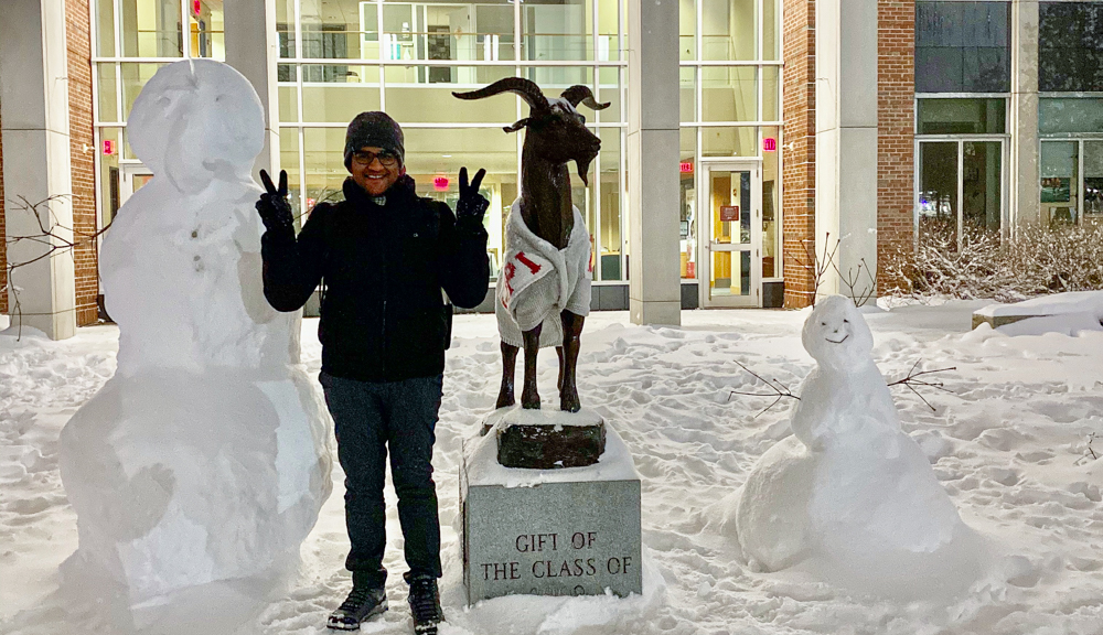 Abhishek Jain poses in front of the Gompei statue and two snowmen on the Quad.