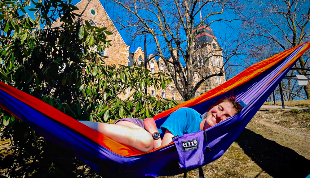 Erika Wentz smiles while lounging in a hammock in front of Boynton Hall.