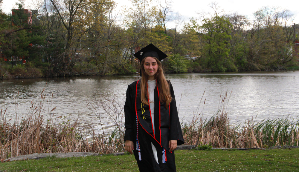 Zeynep Seker smiles in front of a lake while wearing her Commencement robes.