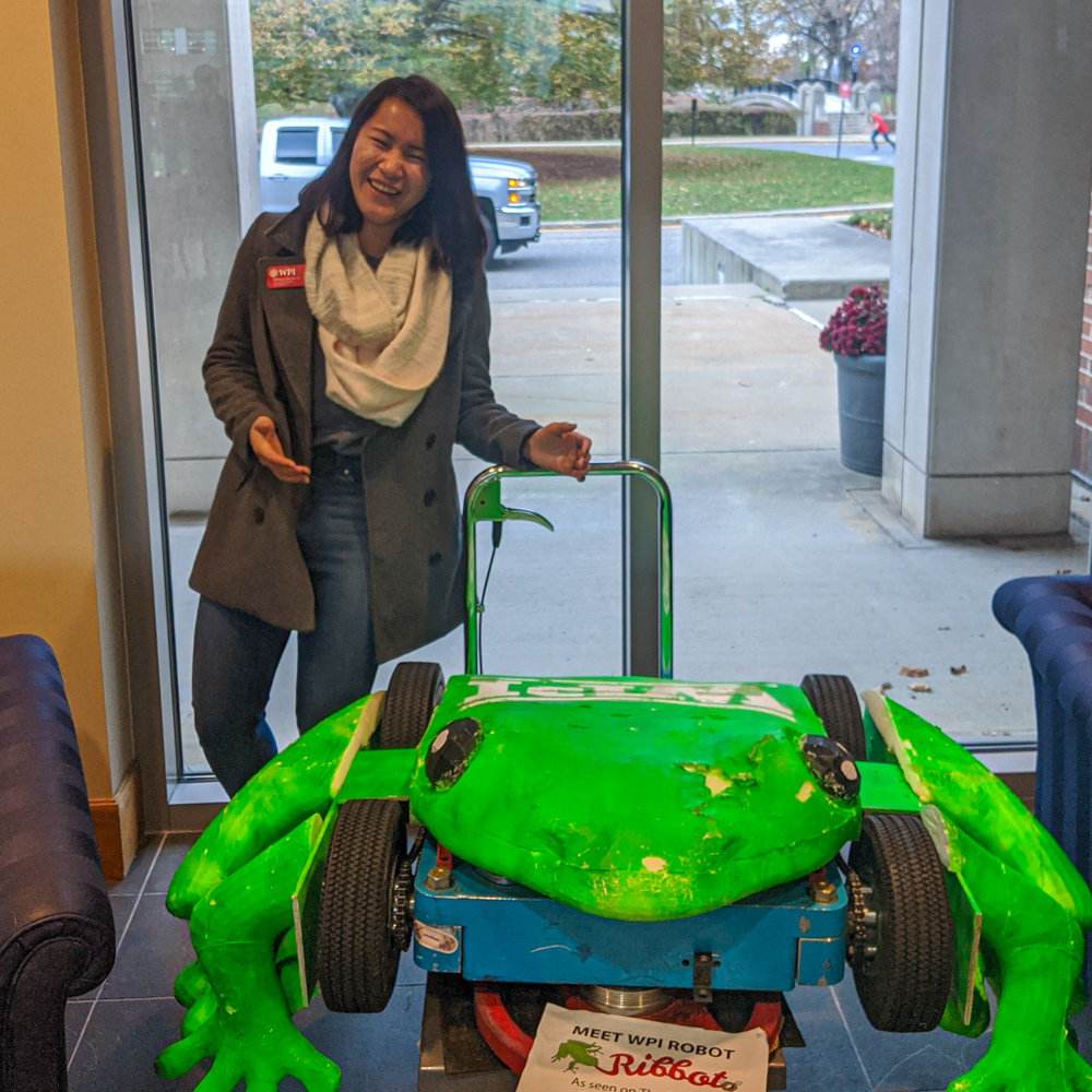 Rebecca Serven smiles while standing behind the Ribbot robot frog.