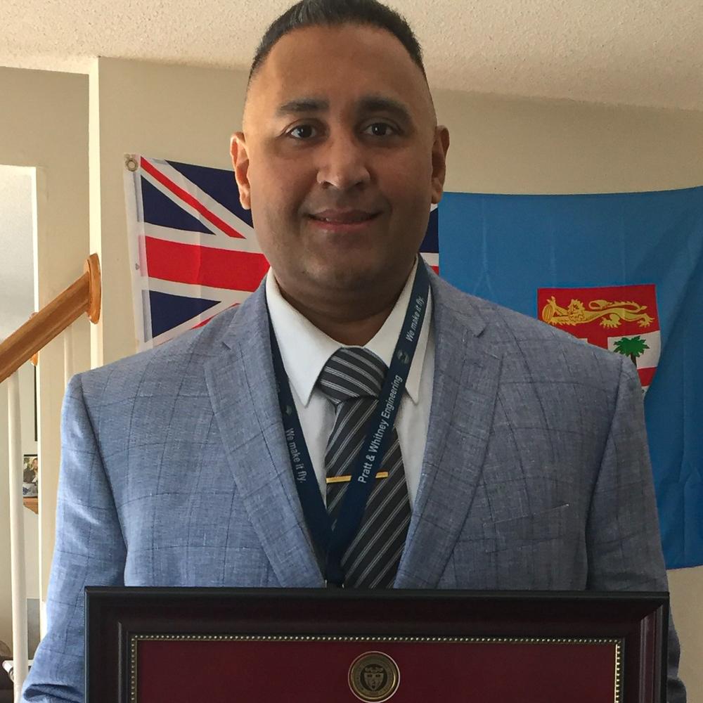 Nathaniel Prasad poses with his framed diploma.