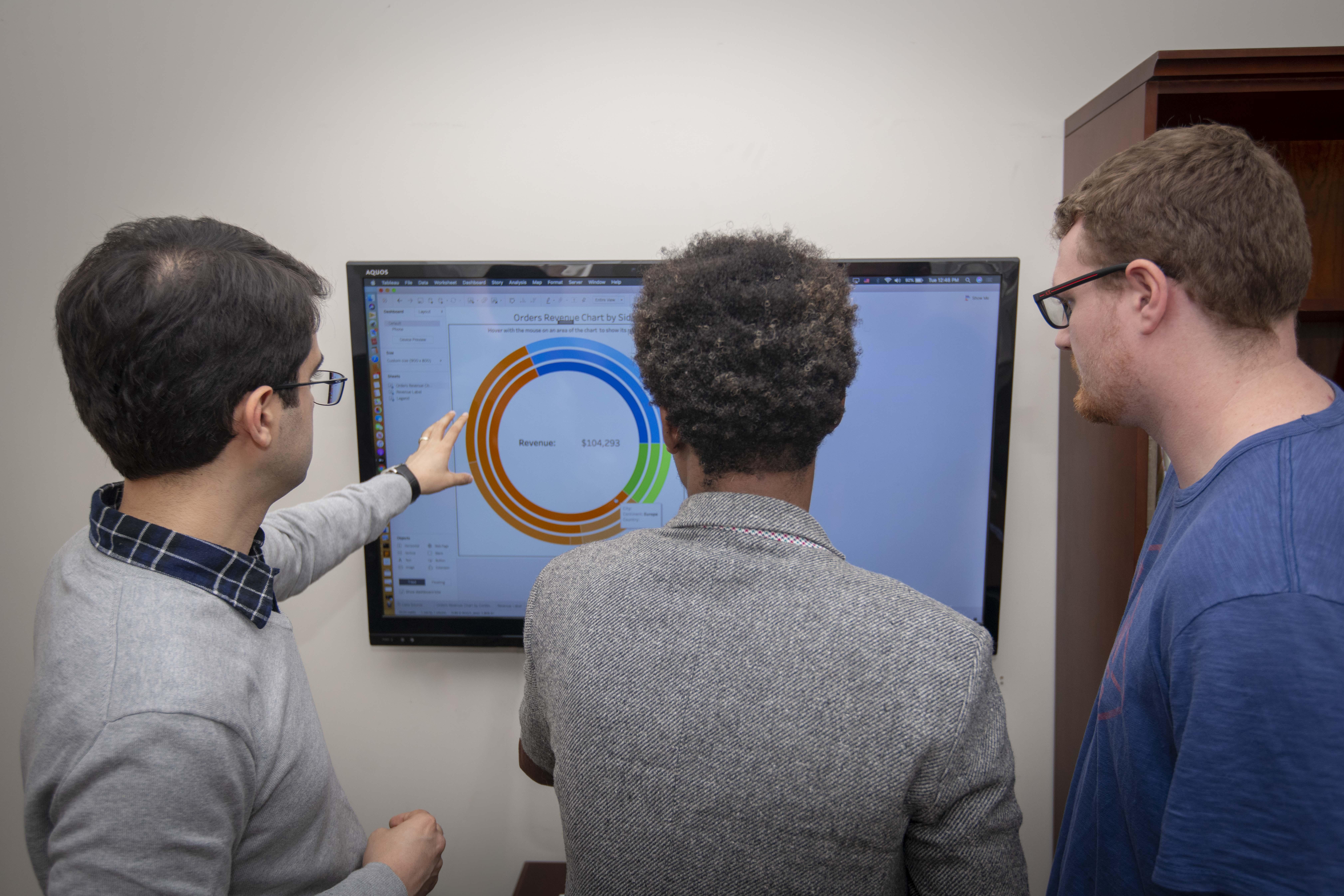 Three men at a data whiteboard.