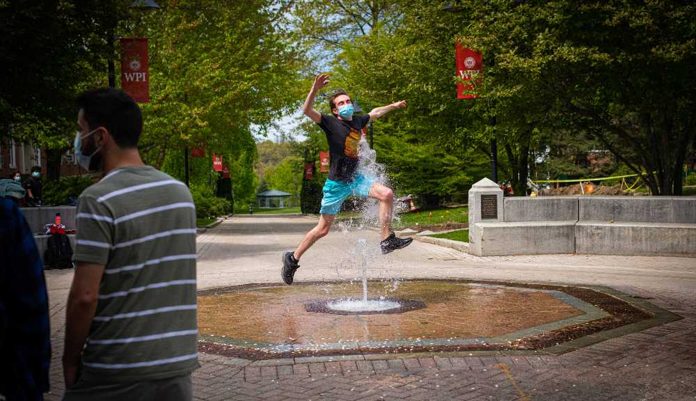 A student jumps through the fountain in the middle of campus.